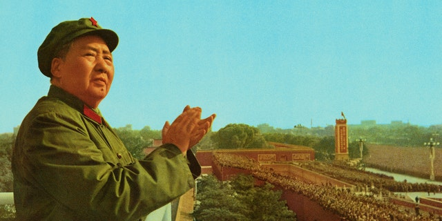 Peking, China: General view of Mao Zedong, the late Chinese Party Communist Chairman, applauding as he stands on a platform overlooking a crowd.