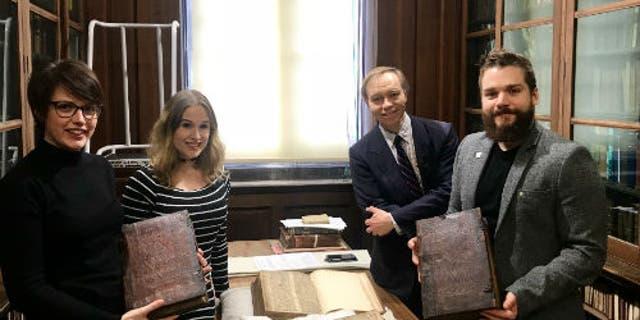 Слева направо: Лия Тетер, Лора Чухан Кэмпбелл, Майкл Ричардсон и Бенджамин Пол с книгами в комнате редких книг Центральной библиотеки Бристоля