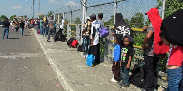 Around 300 migrants wait on the international bridge which divides Mexico and Guatemala. (GDA via AP Images)