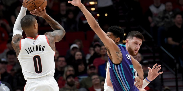 Portland Trail Blazers guard Damian Lillard, left, shoots a basket over Charlotte Hornets guard Jeremy Lamb, center, as center Jusuf Nurkic, right, sets a pick during the first half of an NBA basketball game in Portland, Ore., Friday, Jan. 11, 2019.