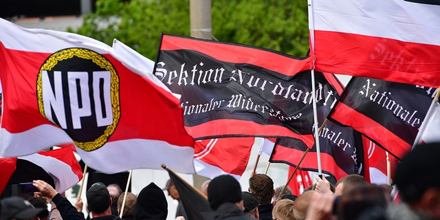 """The flags of """"Sektion Nordland"""" and flags of the far-right NPD political party are seen while gathering to march on May Day on May 1, 2018 in Erfurt, Germany."""