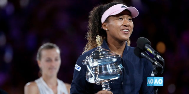 Japan's Naomi Osaka holds her trophy after defeating Petra Kvitova, left, of the Czech Republic during the women's singles final at the Australian Open tennis championships in Melbourne, Australia, Saturday, Jan. 26, 2019.