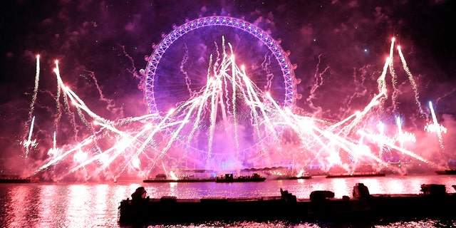 Fireworks explode over the London Eye during the New Year's eve celebrations after midnight in London, Tuesday, Jan. 1, 2019.(AP Photo/Kirsty Wigglesworth)