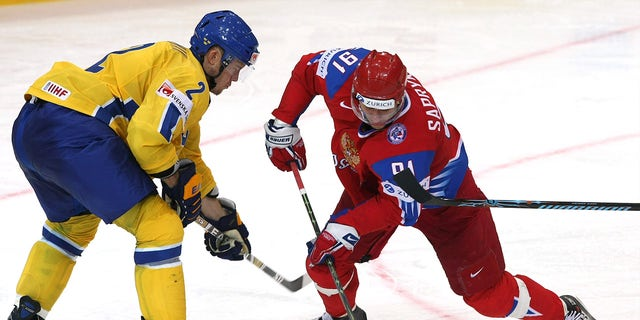 Oleg Saprykin (R) of Russia fights for the puck with Nicklas Grossman (L) of Sweden during the IIHF World Ice Hockey Championship qualification round match between Russia and Sweden on April 30, 2009.