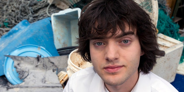FILE - In this May 11, 2017, file photo, Dutch innovator Boyan Slat poses for a portrait next to a pile of plastic garbage prior to a press conference in Utrecht, Netherlands. (AP Photo/Peter Dejong, File)
