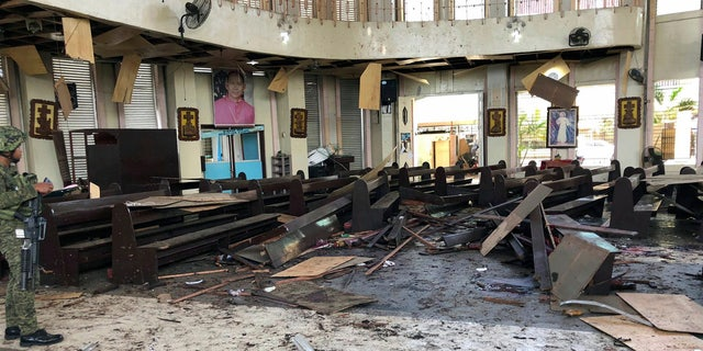 A soldier viewing the site inside a Roman Catholic cathedral in Jolo, the capital of Sulu province in the southern Philippines, after two bombs exploded Sunday. (WESMINCOM Armed Forces of the Philippines Via AP)