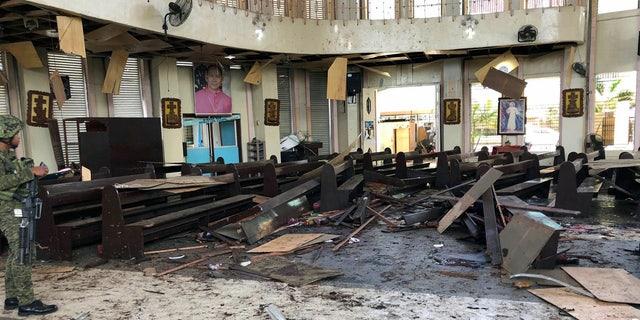 Un soldado que ve el sitio dentro de una catedral católica romana en Jolo, la capital de la provincia de Sulu en el sur de Filipinas, después de que explotaran dos bombas el domingo. (Fuerzas armadas de WESMINCOM de Filipinas vía AP)