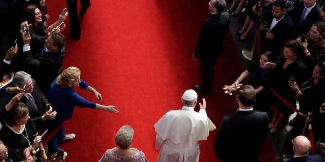 Flanked by Panama's President Juan Carlos Varela, right, and first lady Lorena Castillo, Pope Francis arrives at the foreign ministry headquarters Palacio Bolivar, in Panama City, Thursday, Jan. 24, 2019. (AP Photo/Alessandra Tarantino)