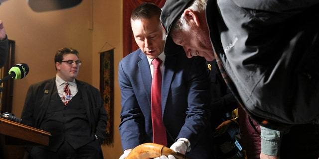 FBI special agent Jake Archer of the FBI Art Crime team holds a powder horn as John Bendzick of Dearborn, right, looks on, during a news conference, Tuesday, Jan. 15, 2019, at the Dearborn Historical Museum in Dearborn, Mich.