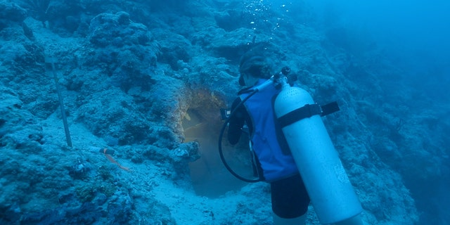 Filmmaker Stephani Gordon records the encrusted cockpit area of the aircraft discovered off the coast of Buka Island. (Stephani Gordon, Open Boat Films)