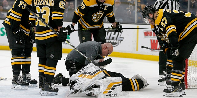Boston Bruins goaltender Tuukka Rask (40) is attended to by medical personnel as his teammates look on after taking a hit on a goal by New York Rangers center Filip Chytil during the first period of an NHL hockey game, Saturday, Jan. 19, 2019, in Boston. (Associated Press)