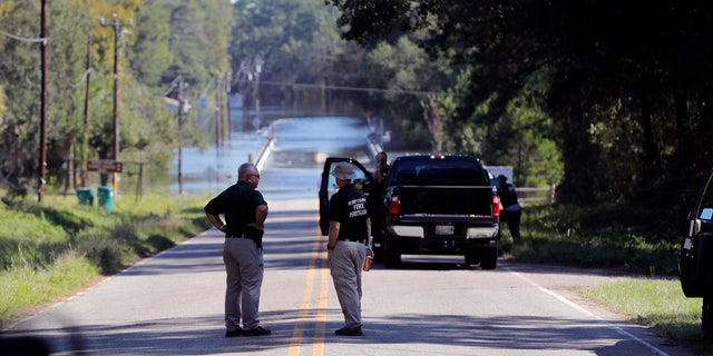 FILE - In this Wednesday, Sept. 19, 2018, file photo, responders congregate near where two people drowned the evening before when they were trapped in a Horry County Sheriff's transport van while crossing an overtopped bridge over the Little Pee Dee River on Highway 76, during rising floodwaters in the aftermath of Hurricane Florence in Marion County, S.C. (AP Photo/Gerald Herbert, File)