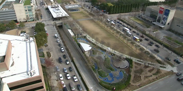 Cars pass under and beside Dallas' Klyde Warren Park.