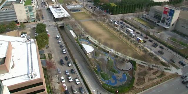 Cars pass under and beside Dallas' Klyde Warren Park.