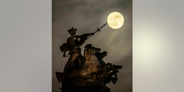 A blood moon, set to be the last of its kind for two years, rises above the 'Maritime Prowess' by Albert Hemstock Hodge on the Guild Hall ahead of the Lunar Eclipse, in Hull, England, Sunday, Jan. 20, 2019.
