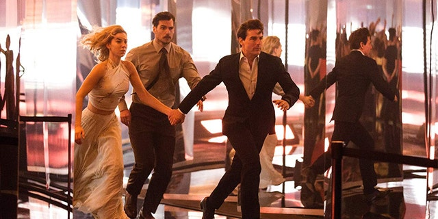 (L-R): Vanessa Kirby, Henry Cavill, and Tom Cruise run from danger in 'Fallout.'