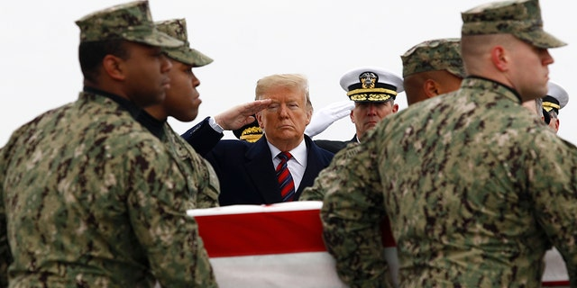 President Donald Trump salutes as a U.S. Navy carry team moves a transfer case containing the remains of Scott A. Wirtz, Saturday, Jan. 19, 2019, at Dover Air Force Base, Del.
