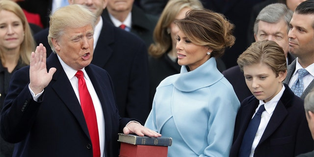 President Trump takes the oath of office as first lady Melania Trump holds the Bible with his son, Barron. (Photo by Chip Somodevilla/Getty Images)