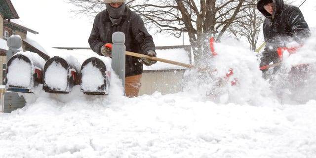 Ausencio Castaneda of Kewaskum, left, clears a path to a series of mailboxes outside a multi-family home with his son Ausencio Castaneda Jr. onMonday, Jan. 28, 2019, in Kewaskum, Wis. A number of inches of snow accumulated in Washington County Sunday Sunday night through Monday. (John Ehlke/West Bend Daily News via AP)