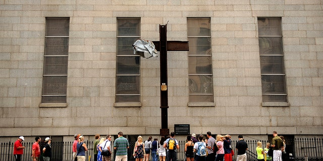 """The Cross at Ground Zero was moved to St. Peter's Church on October 5, 2006. Visitors pass by on Church Street between Barclay and Vesey Streets. A welded steel plaque reads """"The Cross at Ground Zero - Founded September 13, 2001; Blessed October 4, 2001; Temporarily Relocated October 5, 2006. Will return to WTC Museum, a sign of comfort for. Joe Amon, The Denver Post (Photo By Joe Amon/The Denver Post via Getty Images)"""