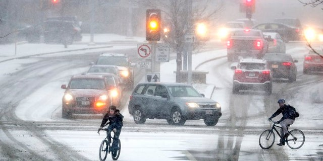 Bikers crossing Park Street at the intersection of University Ave during a late afternoon snow storm Friday, Jan. 18, 2019 in Madison, Wis.