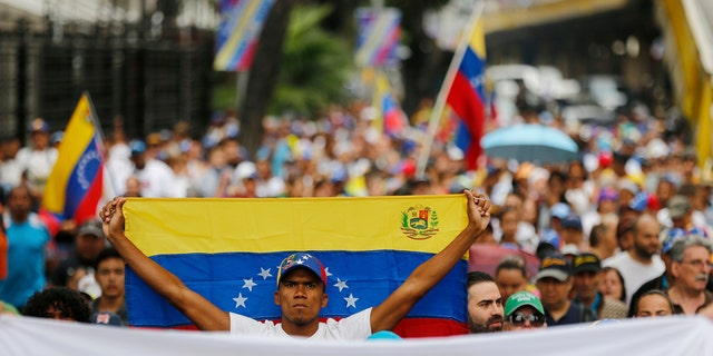 An opposition member holds a Venezuelan national flag during a protest march against President Nicolas Maduro in Caracas, Venezuela, Wednesday, Jan. 23, 2019. Venezuela's re-invigorated opposition faces a crucial test Wednesday as it seeks to fill streets nationwide with protesters in an appeal to the military and the poor to shift loyalties that until recently looked solidly behind Maduro's government. (AP Photo/Fernando Llano)