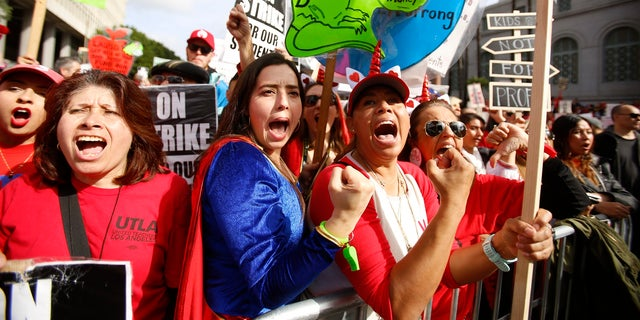 Elementary school teachers Iris Marin, second from left, center, and Mireya Gutierrez, right, and Lorena Redford, rally in downtown Los Angeles, Friday, Jan. 18, 2019.