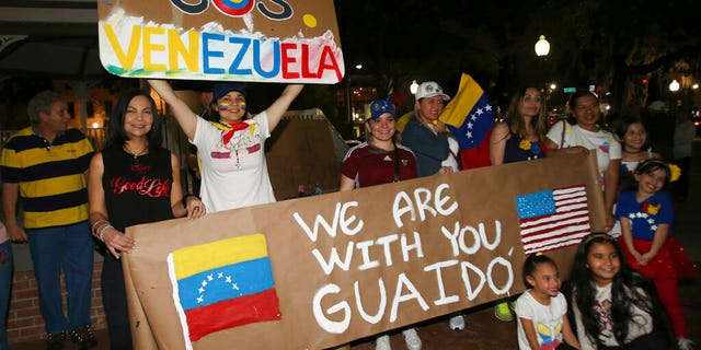 People hold signs and pose for pictures as they protest against Venezuelan President Nicolas Maduro with about 150 other people on the Ocala Downtown Square in Ocala, Fla., Wednesday, Jan. 23, 2019. The protestors in Ocala joined thousands of Venezuelans who took to the streets in Caracas, Venezuela, Wednesday, answering the opposition's call for a nationwide protest to rid Maduro from the office. (Bruce Ackerman/Star-Banner via AP)