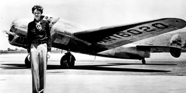 Amelia Earhart stands in front of her Lockheed Electra.