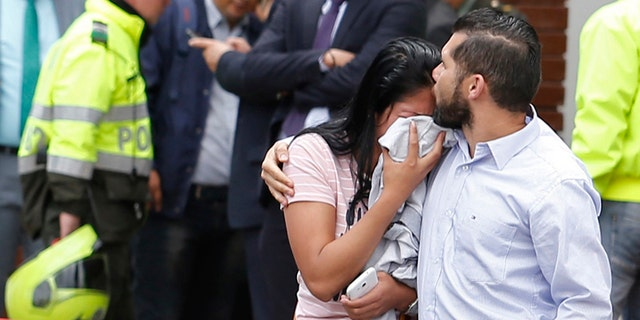 Family members of victims of a bombing embrace outside the entrance to the General Santander police academy where the bombing took place in Bogota, Colombia, Thursday.