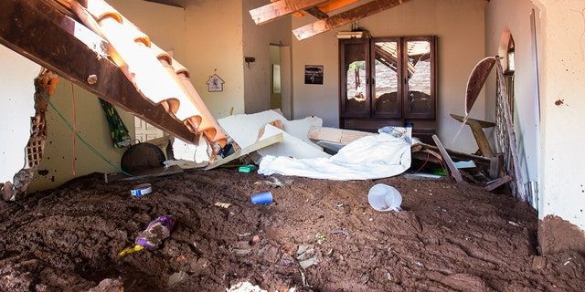 Drying mud lies high in a house affected by the mud avalanche caused by the broken dam. (Photo by Rodney Costa/picture alliance via Getty Images)