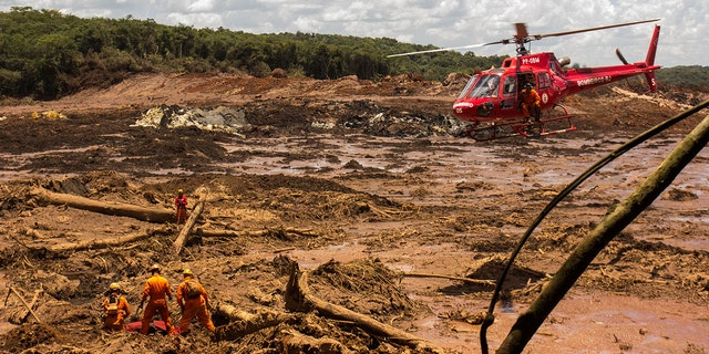 On Tuesday in Brumadinho, firefighters recover a body with a chopper's assistance. (Photo by Rodney Costa / picture alliance via Getty Images)