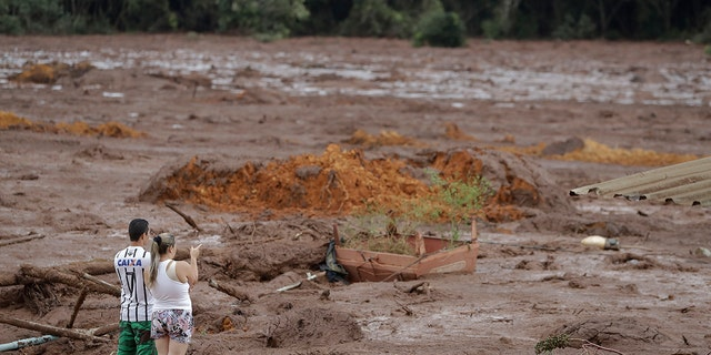 A couple with missing relatives look at the flooded area, after a dam collapsed in Brumadinho, Brazil, Saturday, Jan. 26, 2019. (Associated Press)