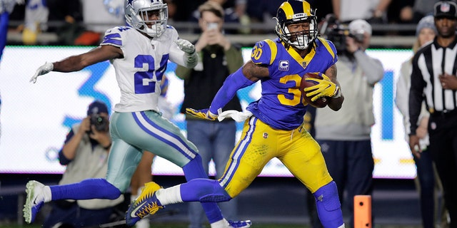 Los Angeles Rams running back Todd Gurley scores past Dallas Cowboys cornerback Chidobe Awuzie during the first half in an NFL divisional football playoff game Saturday, Jan. 12, 2019, in Los Angeles. (Associated Press)