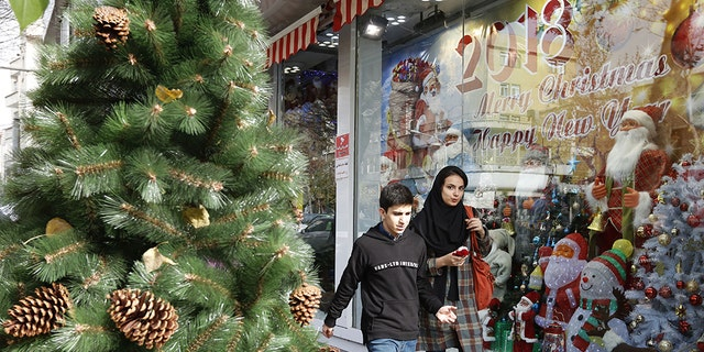 Iranians walk past Christmas decorations in a street in the capital Tehran on December 24, 2017, on Christmas eve.