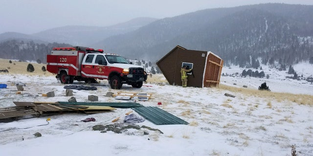 A woman and two cats were inside the tiny house when it was blown away by fierce winds, according to fire officials.