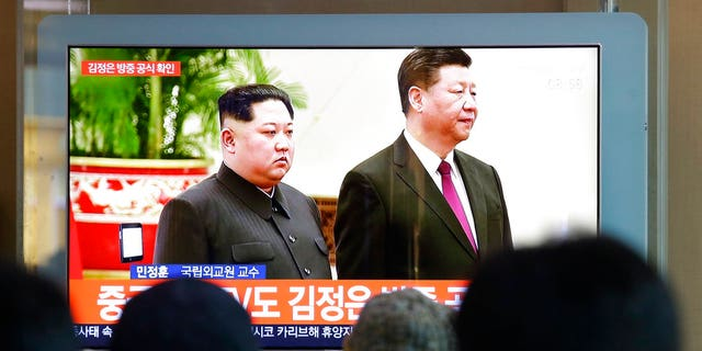 People watch a TV screen showing file footage of North Korean leader Kim Jong Un and Chinese President Xi Jinping, right, during a news program at the Seoul Railway Station in Seoul, South Korea.