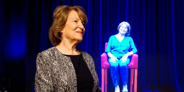 In this October 2017 photo, Holocaust survivor Fritzie Fritzshall stands in front of a hologram of herself at The Abe & Ida Cooper Survivor Stories Experience in the Illinois Holocaust Museum & Education Center in Skokie, Ill. (Ron Gould/Illinois Holocaust Museum & Education Center via AP)