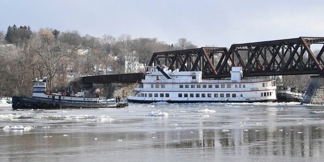 Crews from the tugboats Frances, left, and Margot work to free the Captain J.P. III cruise ship that broke away from its winter moorings in Troy, N.Y., and floated down river.