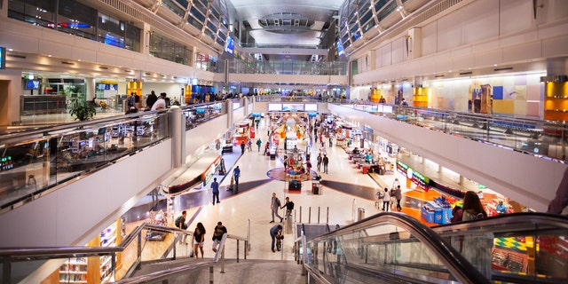 Dubai, United Arab Emirates - September 14, 2016: Night shot of modern duty free area in transit of new terminal for A 380 in airport Dubai. People are walking on both levels.