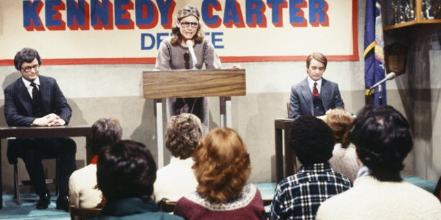 "Bill Murray as Ted Kennedy, Jane Curtin as moderator, Brian Doyle-Murray as Jody Powell during ""Kennedy-Powell Debate"" skit on February 16, 1980. (NBC/NBCU Photo Bank via Getty Images)"