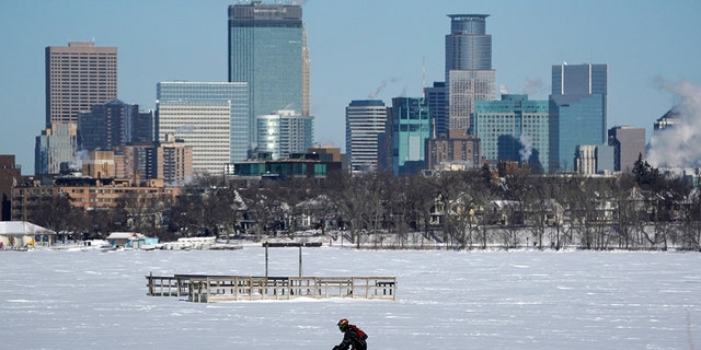 A cyclist decked out in cold weather gear rides past the city skyline and a frozen Bde Maka Ska in Minneapolis. (Anthony Souffle/Star Tribune via AP)