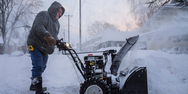 Mike Johnson snow blows his driveway Monday, Jan. 28, 2019, in Rochester, Minn.