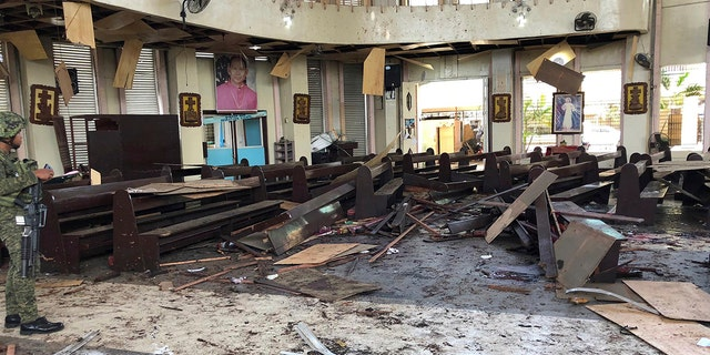 A soldier views the site inside a Roman Catholic cathedral in Jolo, the capital of Sulu province in the southern Philippines after two bombs exploded Sunday, Jan. 27, 2019. (WESMINCOM Armed Forces of the Philippines Via AP)