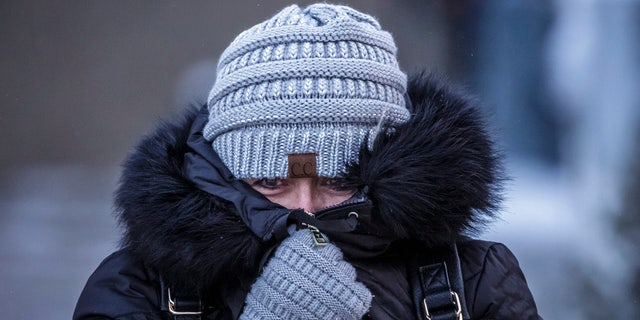 Andrea Billings keeps her face covered while walking across Center Street at its intersection with 1st Avenue in subzero temperatures on the way to her car after work Tuesday, Jan. 29, 2019, in downtown Rochester, Minn.
