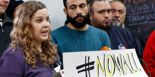 Furloughed National Park Service ranger Sean Ghazalam, second from left, listens as fellow furloughed park ranger Kathryn Gilson speaks during a press conference and rally, Thursday, Jan. 10, 2019, at La Colmena Center in the Staten Island borough of New York city. (AP Photo/Kathy Willens)
