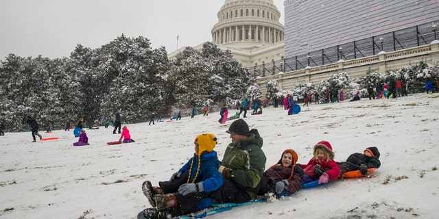 People sled on Capitol Hill as a winter storm arrives in the region, Sunday, Jan. 13, 2019, in Washington.