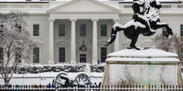 Snow blankets a statue of Andrew Jackson in Lafayette Square with the White House behind, as a winter storm arrives in the region, Sunday, Jan. 13, 2019, in Washington.