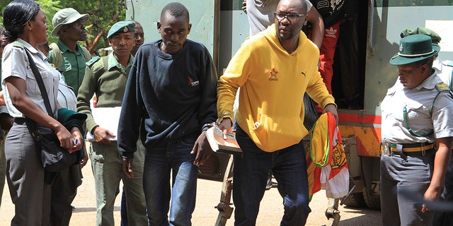 Pastor and activist Evan Mawarire, right, arrives handcuffed at the magistrates courts in Harare, Zimbabwe, Friday.