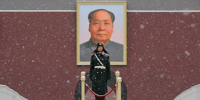 Chinese paramilitary policemen stand guard under the portrait of former leader Mao Zedong outside the Tiananmen Gate as snow falls in Beijing, Tuesday, Feb. 12, 2019. The Pentagon cited competition from countries like China and Russia in its new strategy document on artificial intelligence. (AP Photo/Andy Wong)